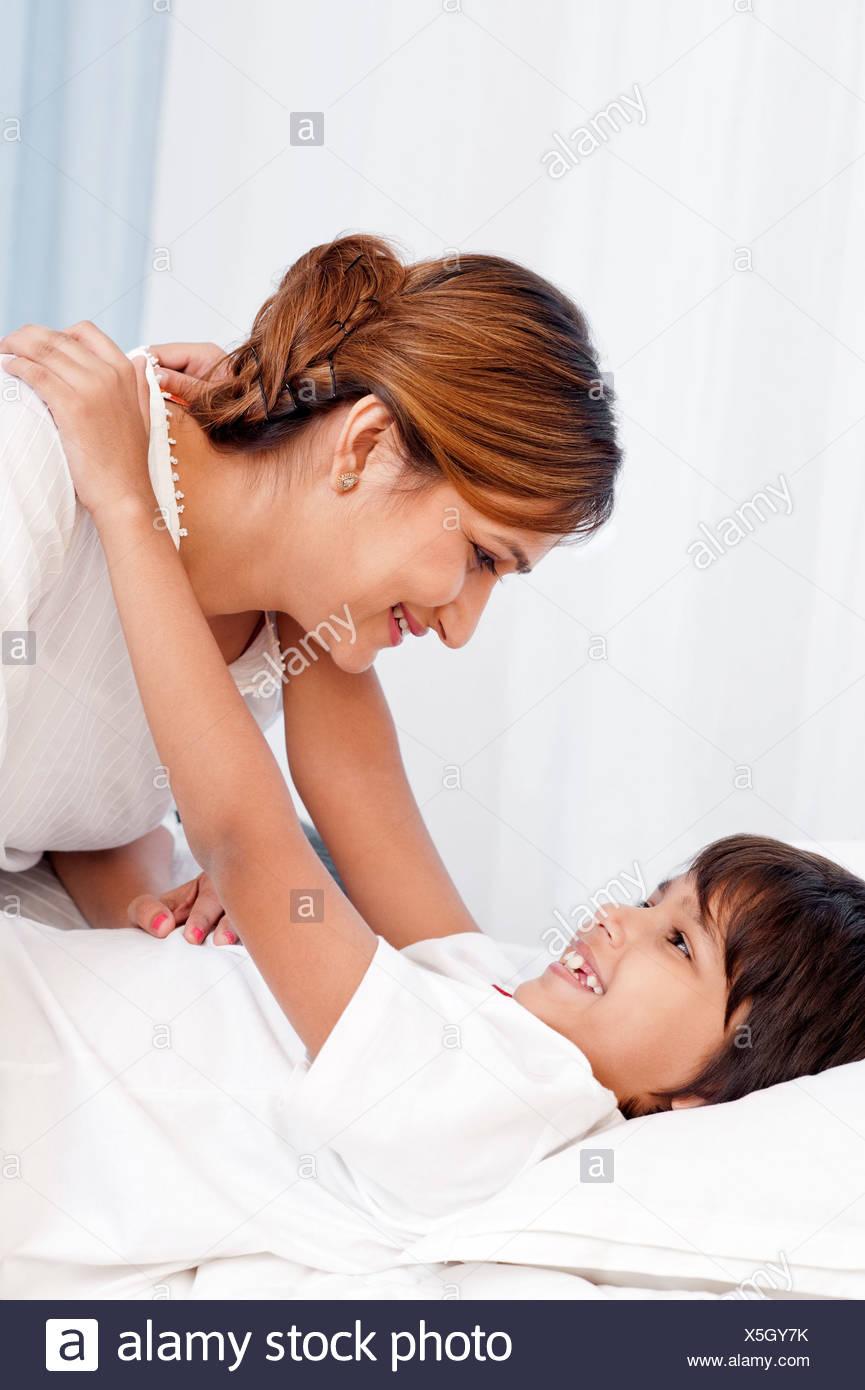 Junge umarmt seine Mutter auf dem Bett Stockbild