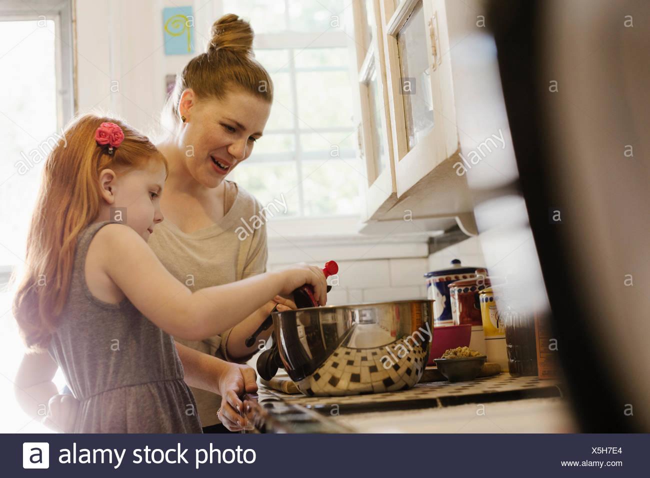 Mitte Erwachsene Mutter gibt Tochter eine helfende hand in Küche Stockbild
