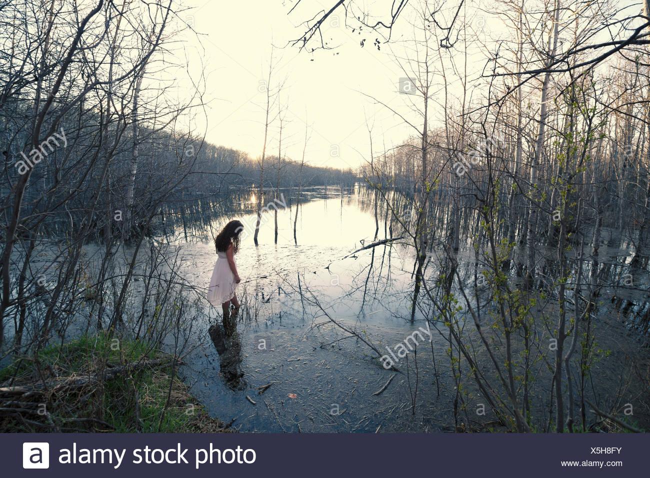 Eine Frau in einem weißen Kleid waten im seichten Wasser in der Abenddämmerung. Stockfoto