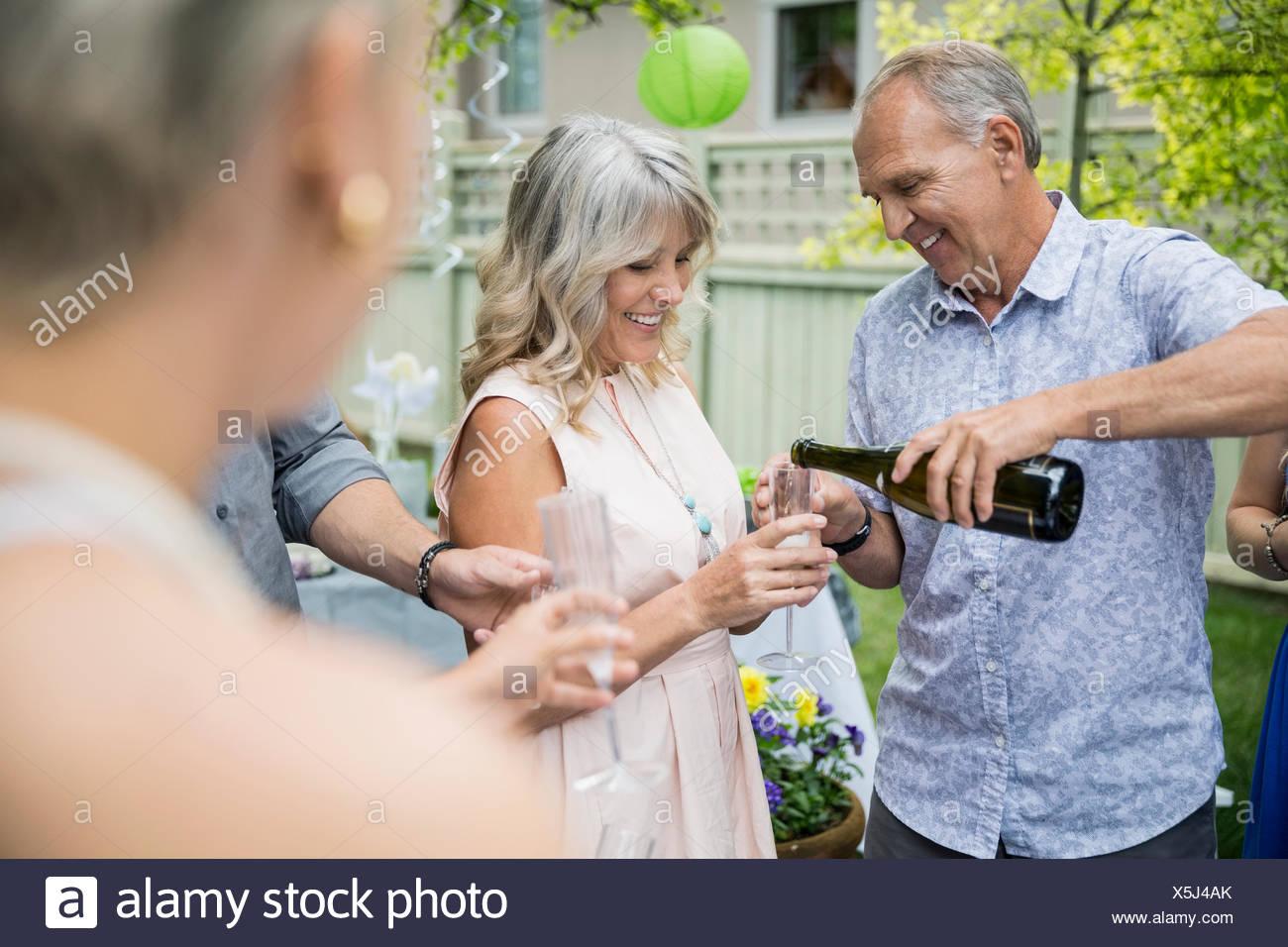 Ehemann Gießen Champagner für Frau auf Gartenparty Stockbild