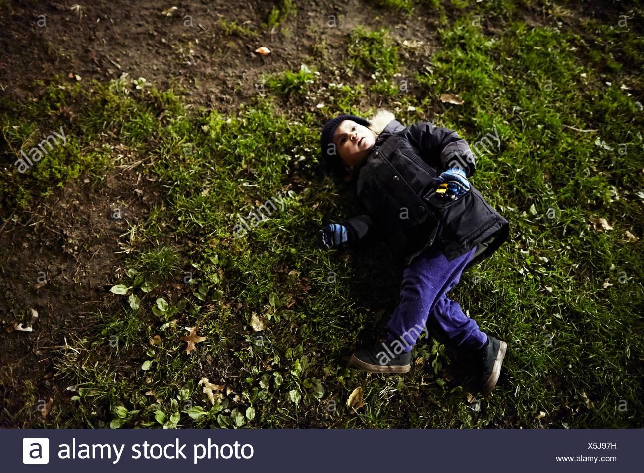 Junge auf dem Rasen liegend Stockbild