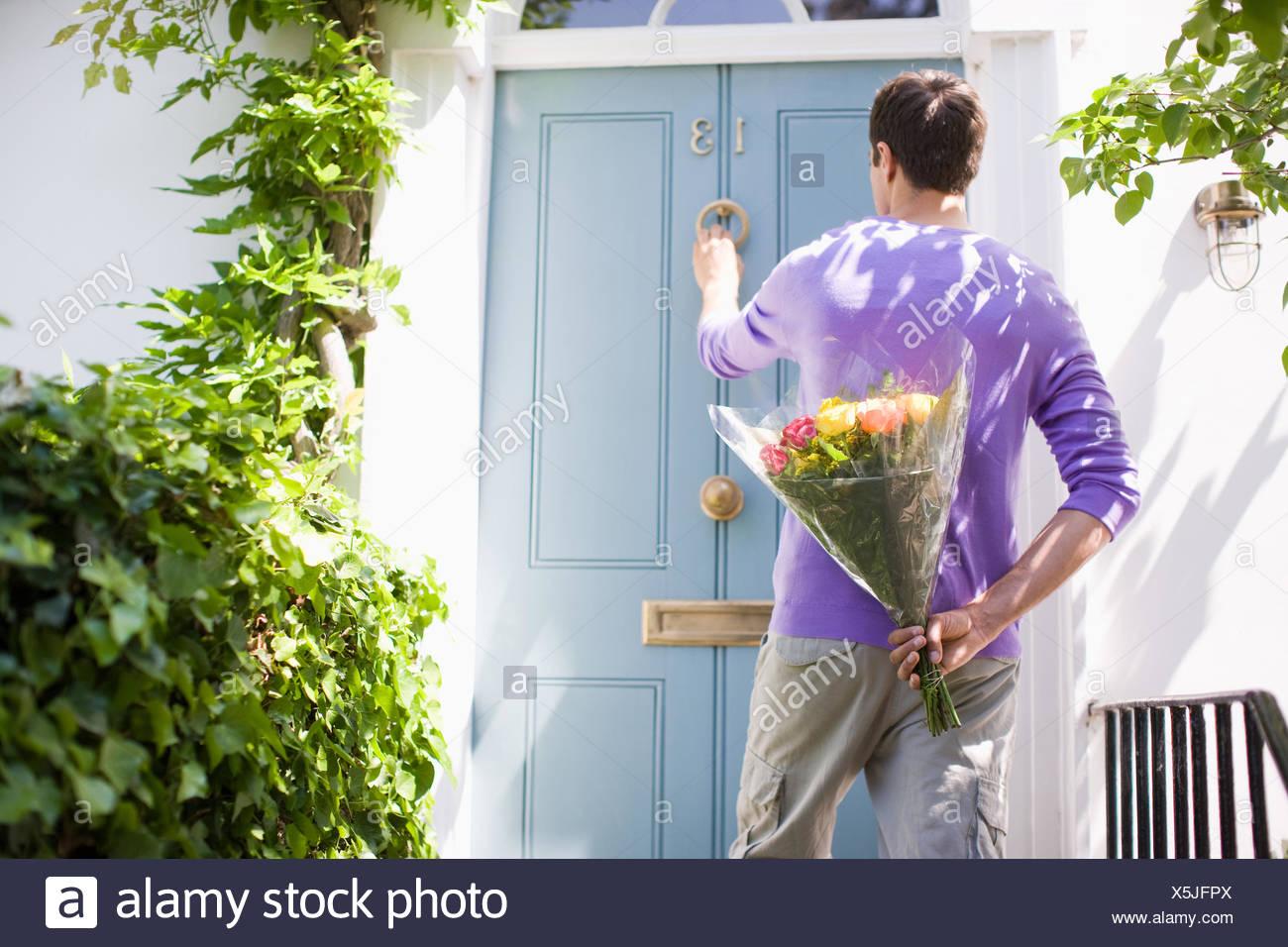Mann hält Blumenstrauss und klopfen an die Tür Stockbild