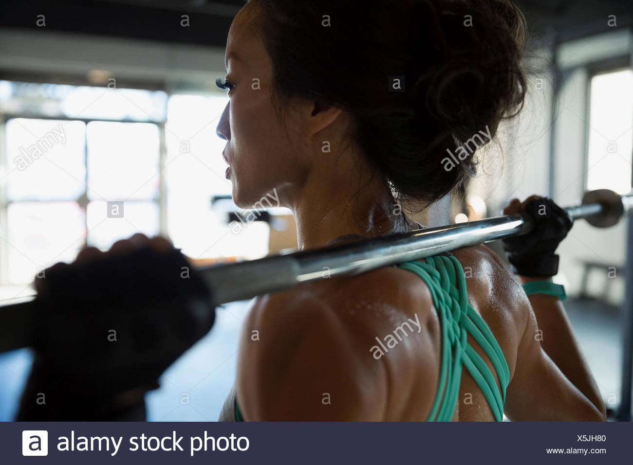 Nahaufnahme von Frau Gewichtheben mit Langhantel in Turnhalle Stockbild