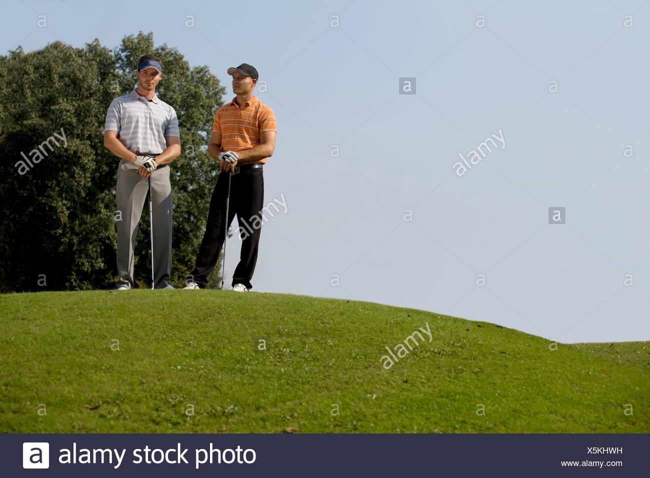 Porträt der jungen Männer stehen mit Golf-Sticks auf Golfplatz Stockbild