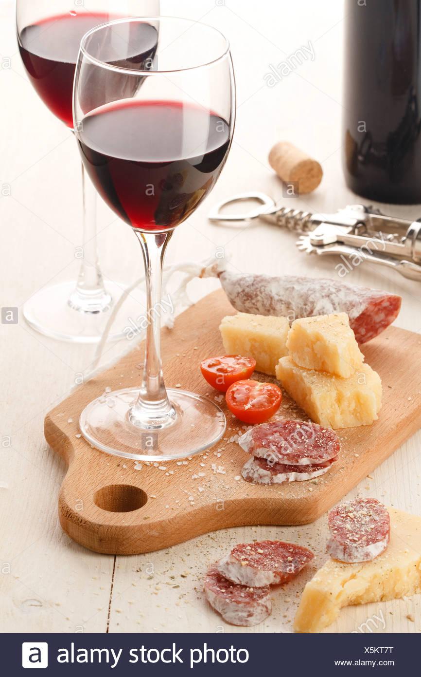 Zwei Weingläser mit Rotwein und Auswahl an Käse und Früchte auf weißem Hintergrund Stockbild