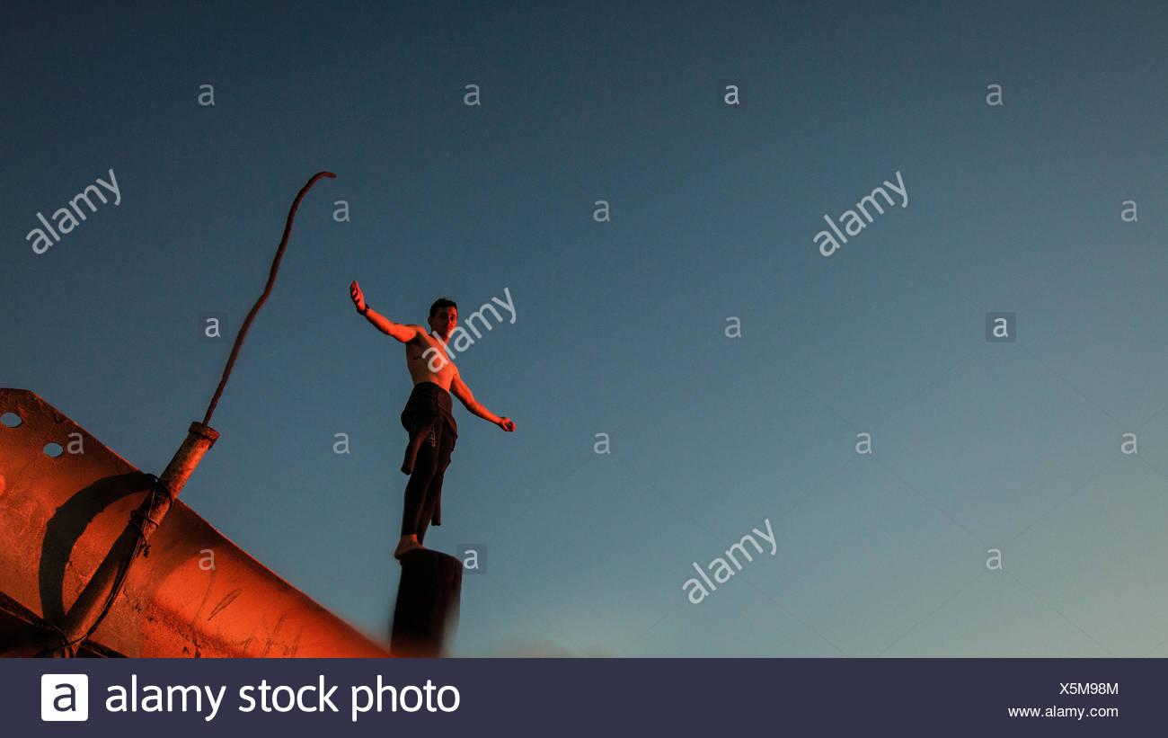 Junge (12-13 Jahre) im Neoprenanzug stehen auf der pole Stockbild