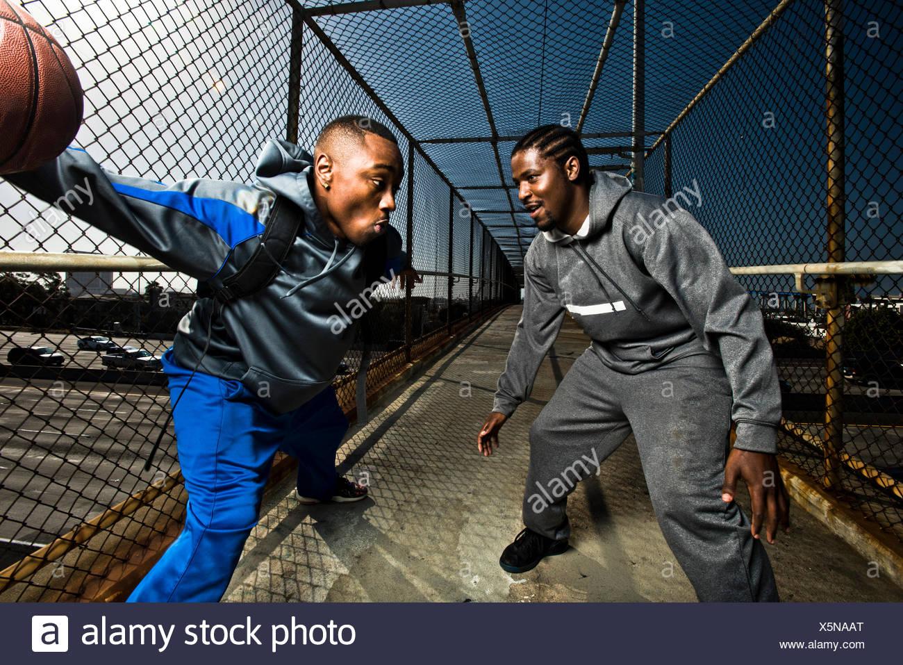 Zwei junge Männer zu Fuß hinunter eine Fußgängerbrücke mit einem Basketball zu spielen. Stockbild