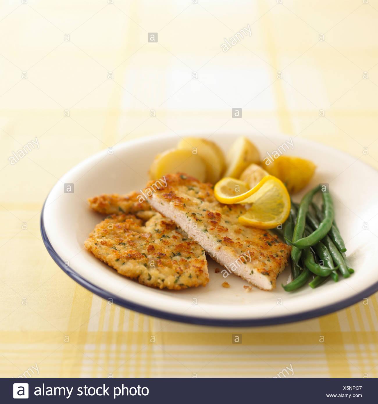 Hähnchen Schnitzel, grüne Bohnen und neuen Kartoffeln auf weißen Teller Stockbild