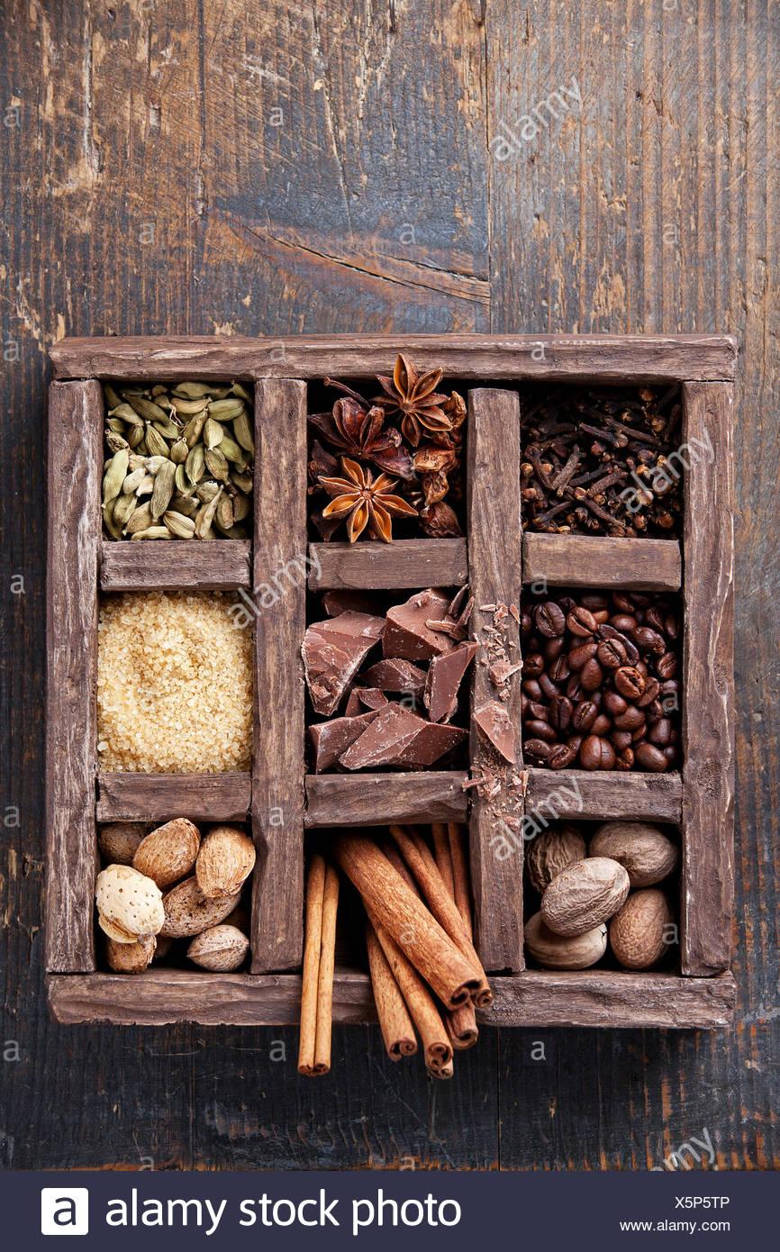 Sortiment an Gewürzen und Kaffeebohnen in Holzkiste Stockbild