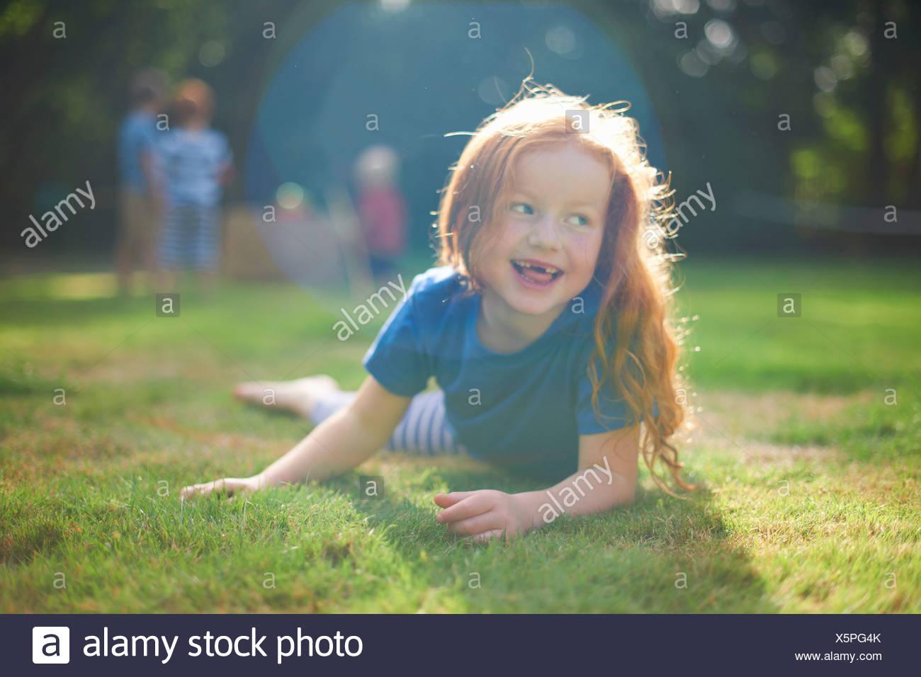 Fröhliches junges Mädchen liegen auf dem Rasen im Garten Stockbild