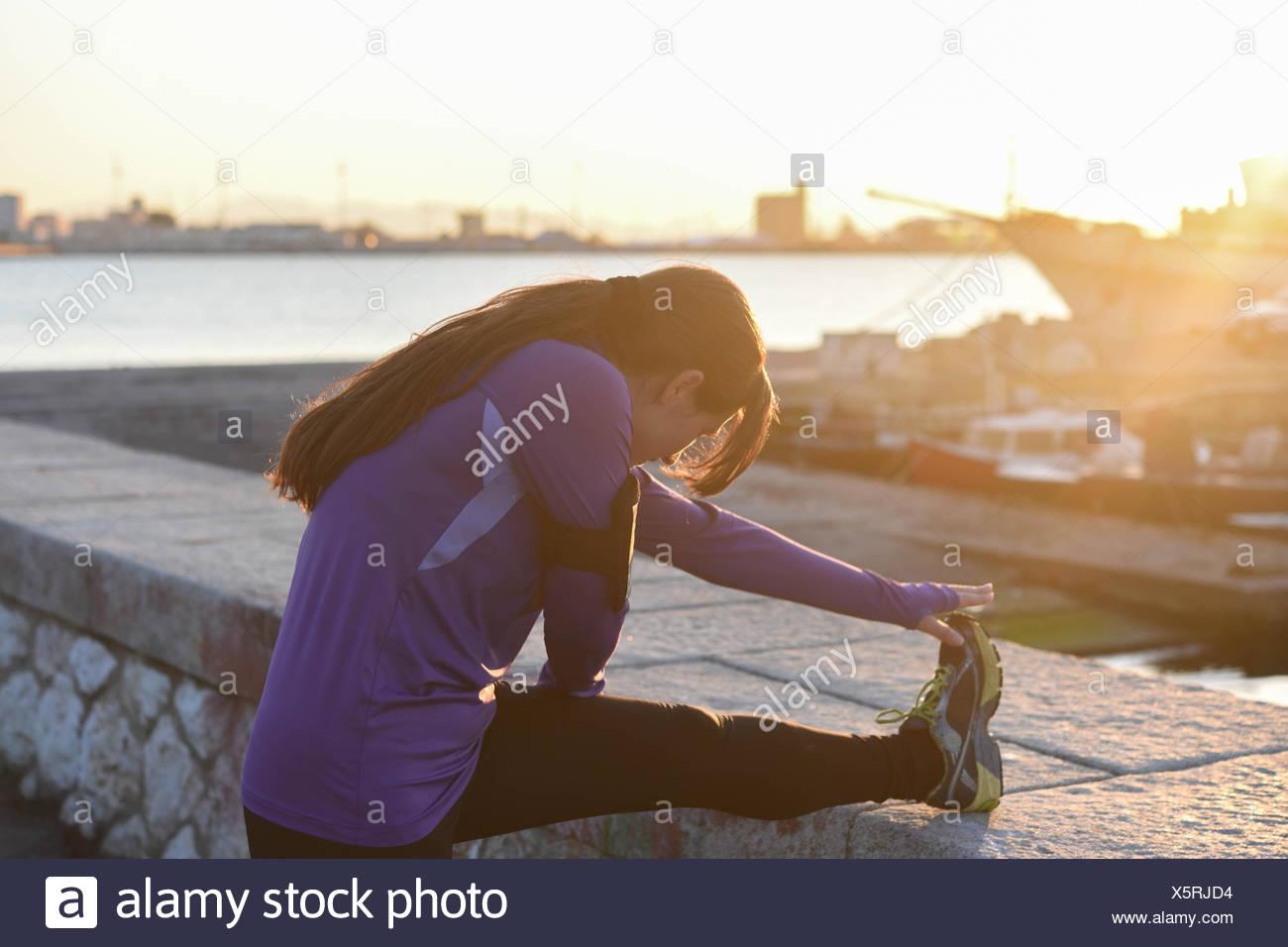Junge Frau dehnen ihr Bein an der Wand bei Sonnenuntergang Stockbild