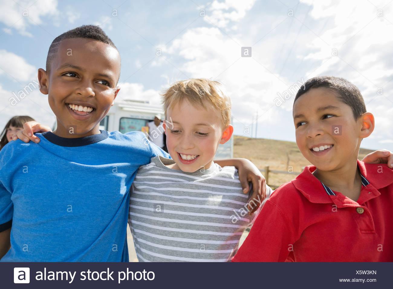 Jungen mit Arme umeinander draußen Stockbild