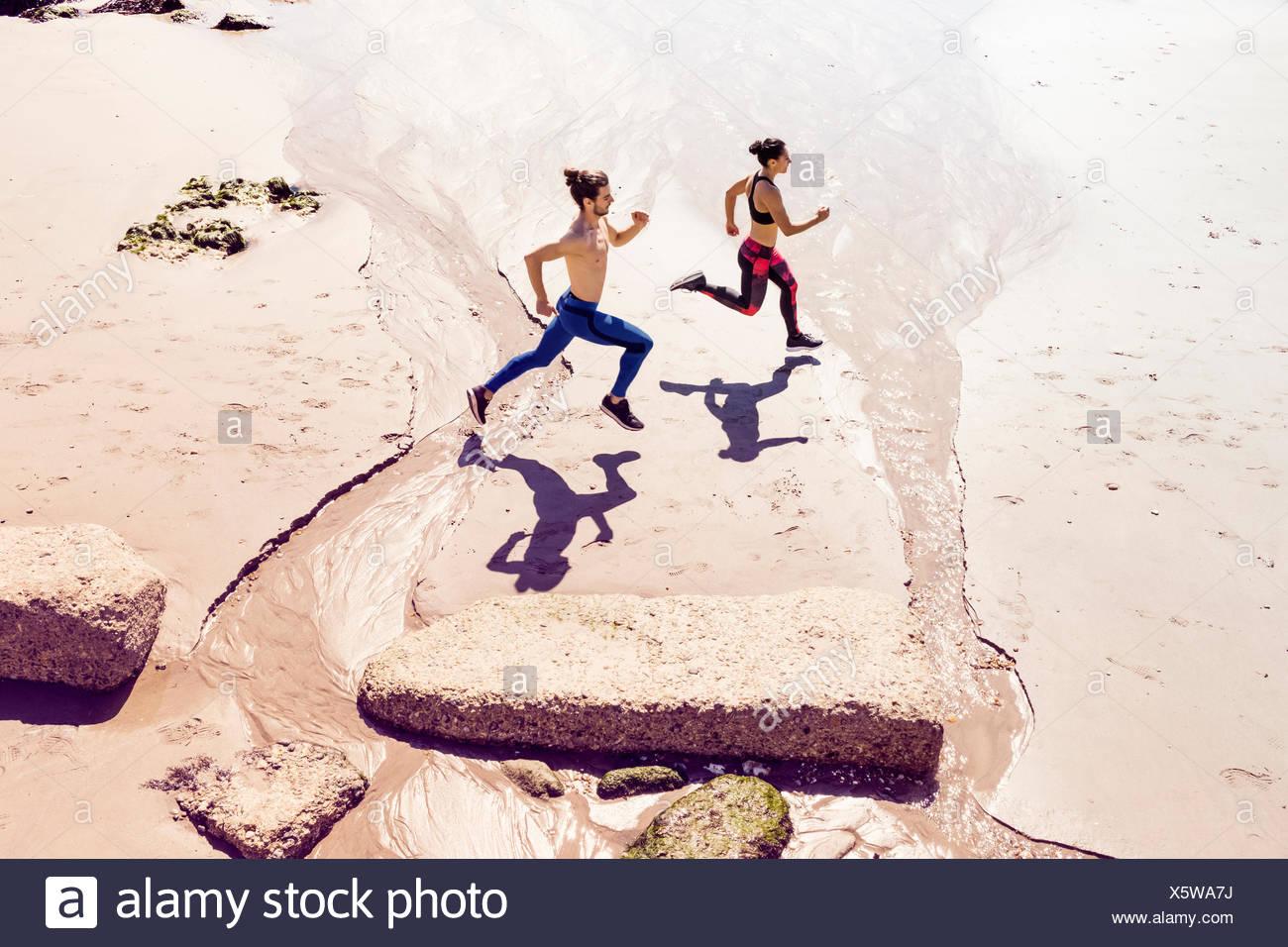 Junger Mann und Frau Strand entlang läuft, Erhöhte Ansicht Stockbild