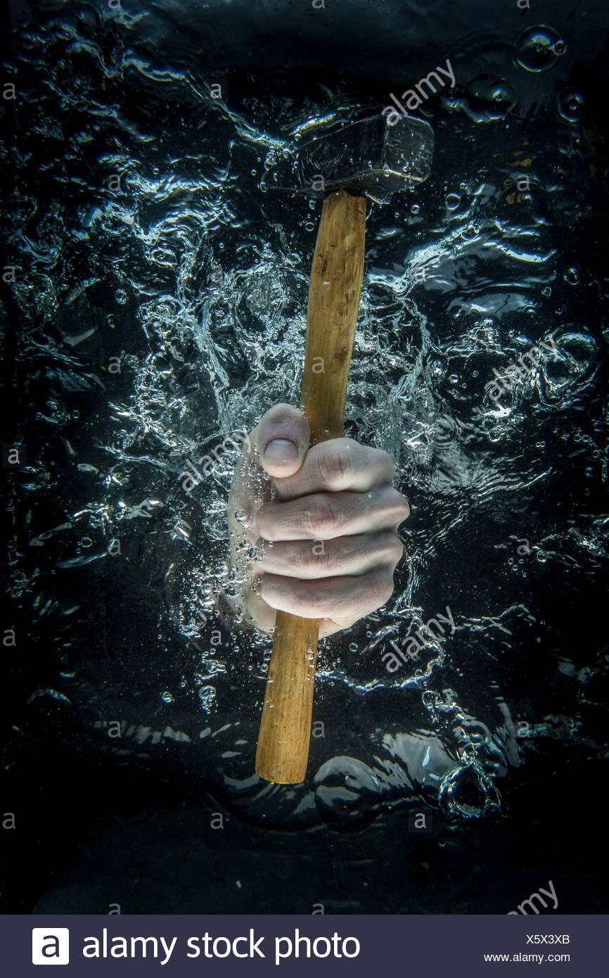 Männliche Hand greifen Hammer unter Wasser Stockbild