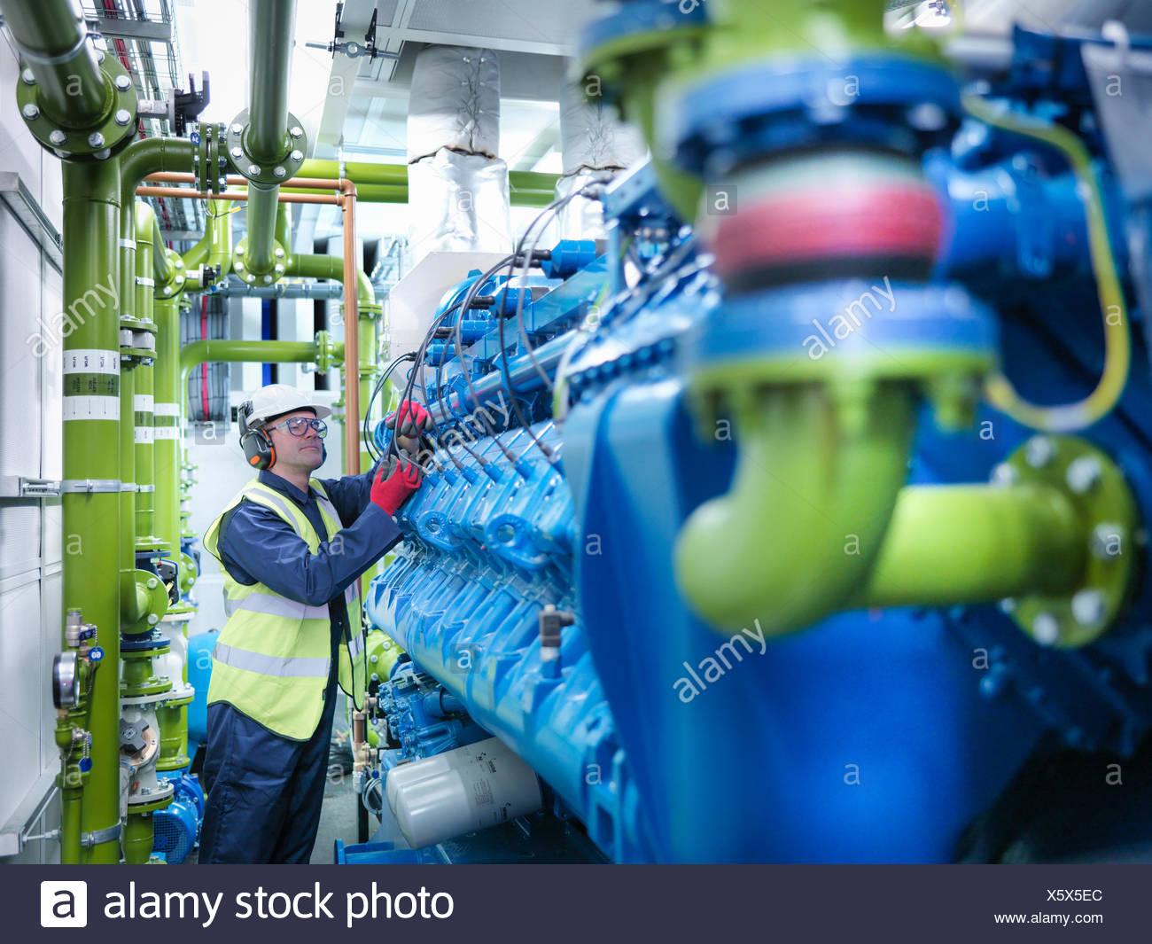 Arbeiter mit Gas befeuert Generator im Kraftwerk gasbefeuert Stockbild