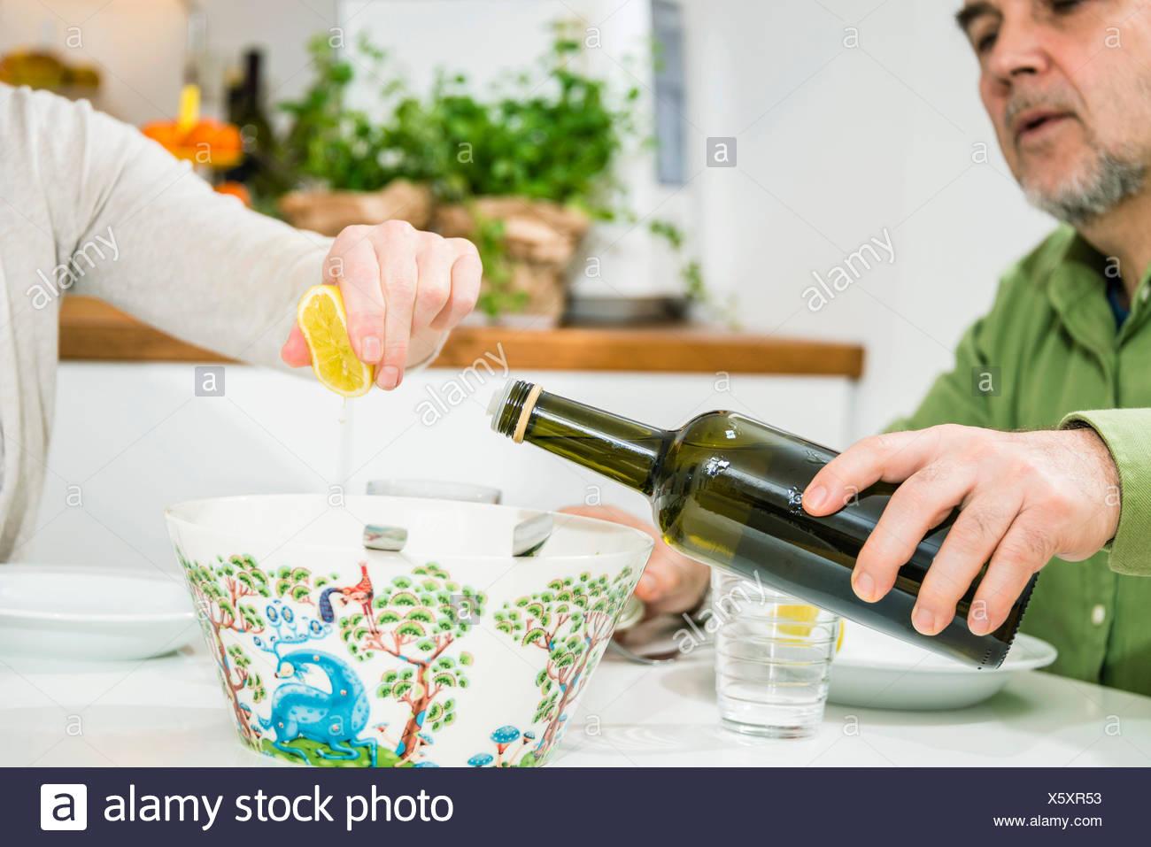 Senior woman goß Öl in Salatschüssel Stockbild