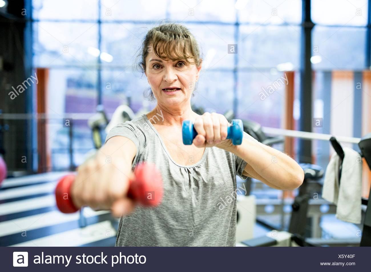 EIGENTUM FREIGEGEBEN. -MODELL VERÖFFENTLICHT. Porträt senior Frau mit Hantel im Fitness-Studio. Stockfoto