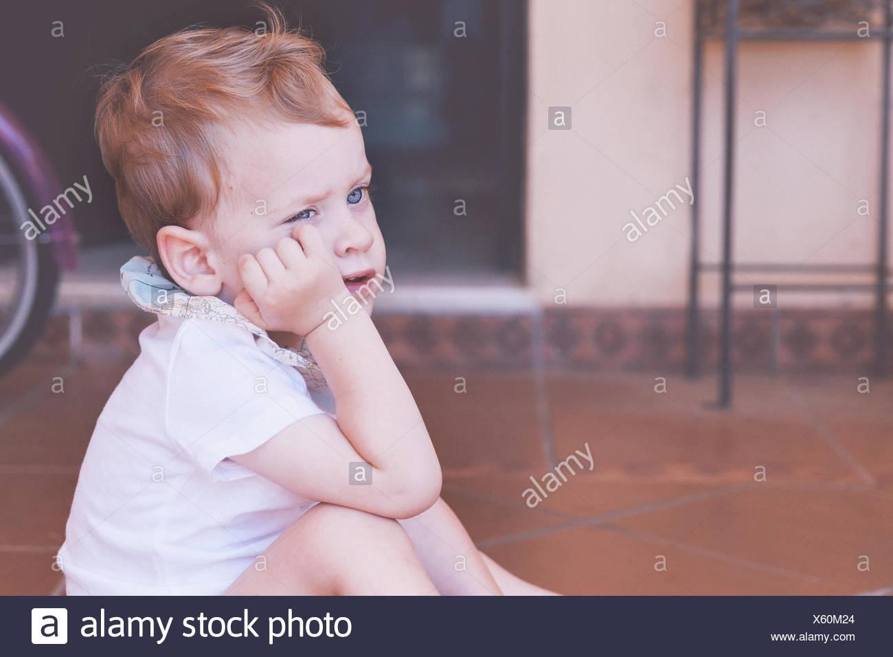 Junge sitzt auf Boden mit Hand am Kinn Stockfoto