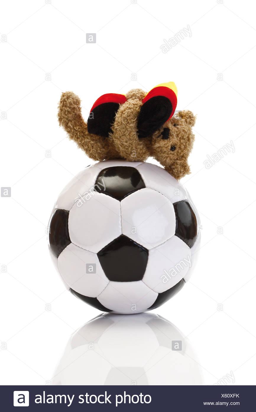 Kleinen Teddybär Verlegung auf Fußball, umarmt Kissen, deutschen ...