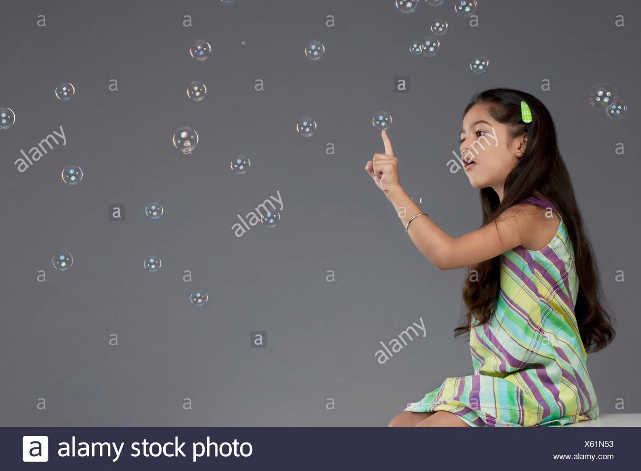Mädchen versucht, eine Blase zu berühren Stockbild