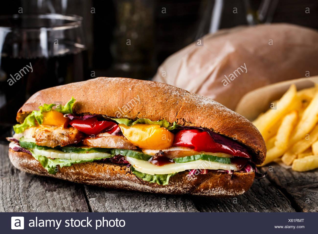 Sandwich mit Huhn, Pommes Frites und Glas Soda auf einem rustikalen Tisch Stockbild