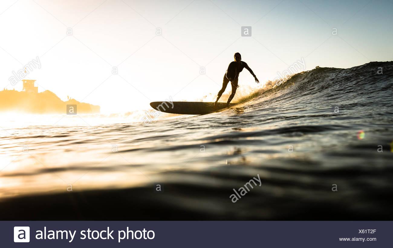 Frau Surfen bei Sonnenuntergang, Malibu, Kalifornien, USA Stockfoto