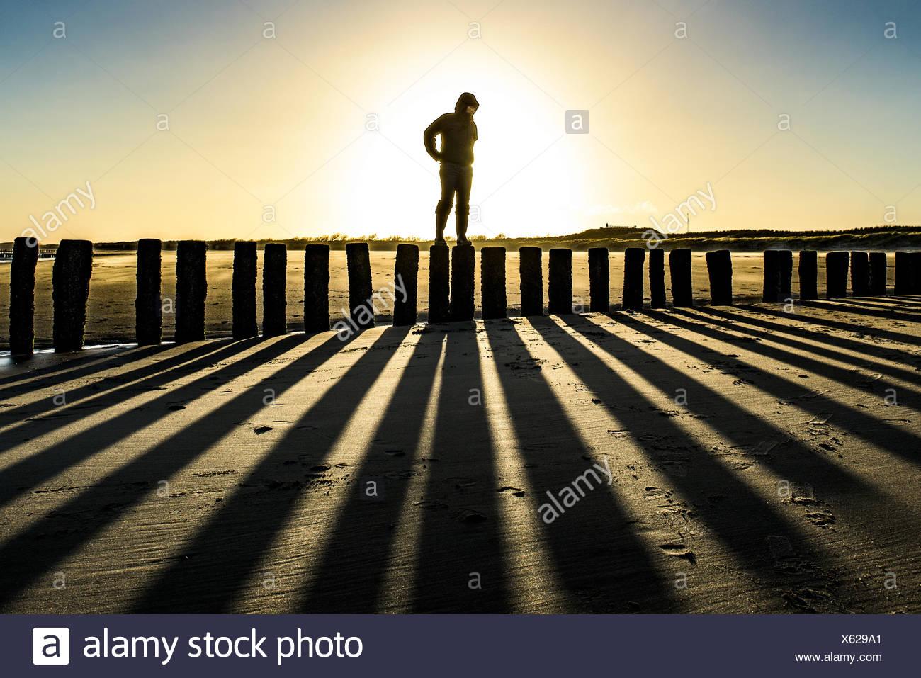 Auf Holzpfosten am Strand gegen Himmel stehende Person Stockbild