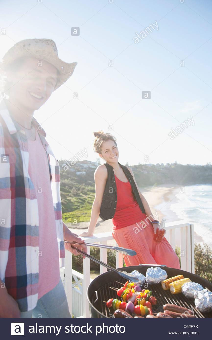 Mann und Frau tendenziell Grill mit Meer im Hintergrund Stockfoto