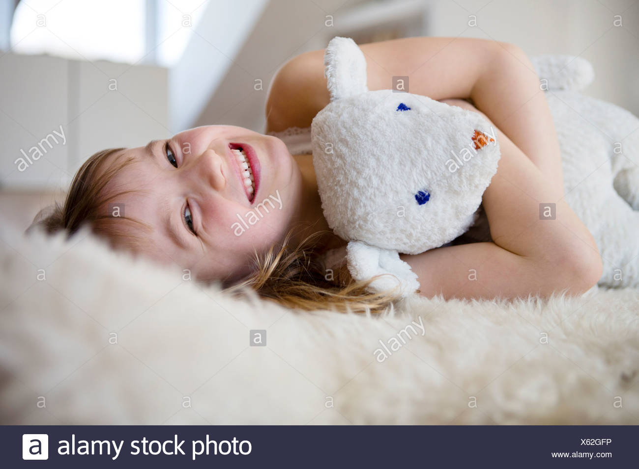 Mädchen auf pelzigen Bett kuscheln Teddybär Stockbild