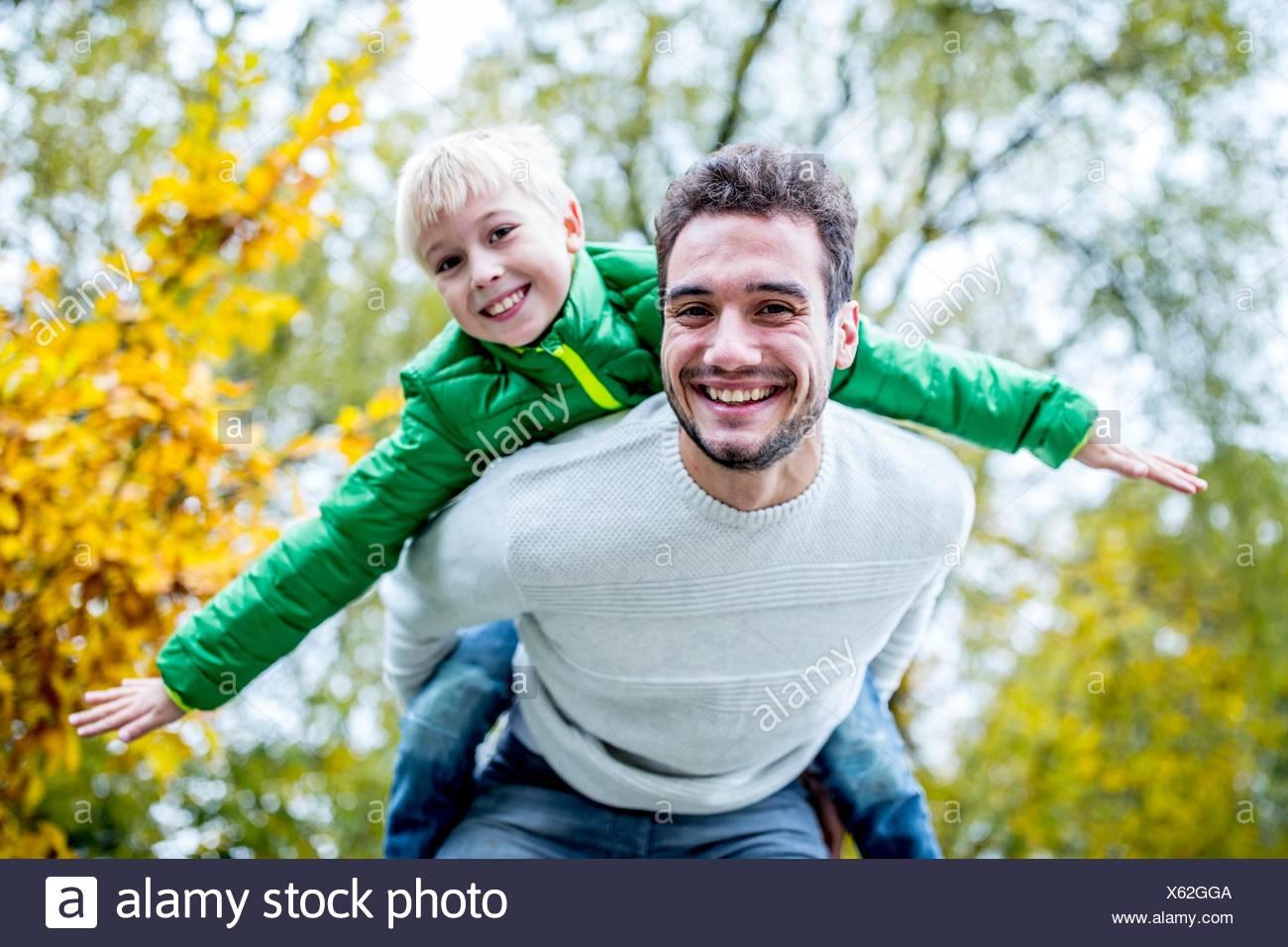 -MODELL VERÖFFENTLICHT. Vater mit Sohn Huckepack im Herbst, Lächeln, Porträt. Stockbild