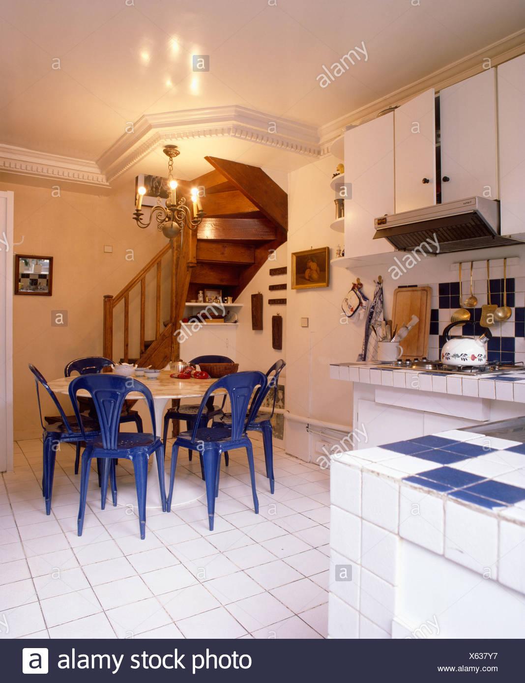 Kronleuchter über dem weißen Tisch mit blauen Stühlen in weiße Küche ...
