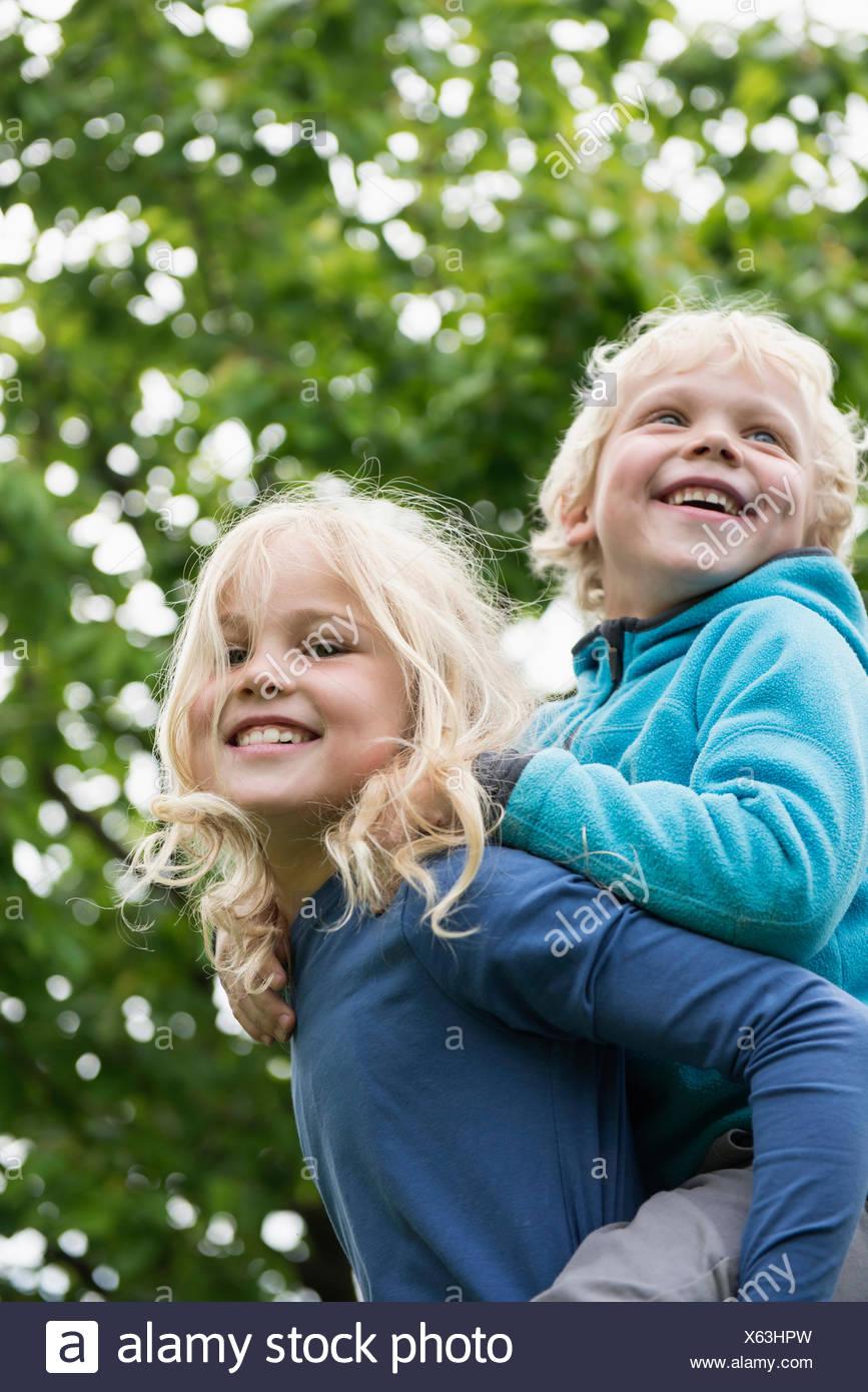Junge blonde Mädchen Bruder Huckepack tragen Stockfoto