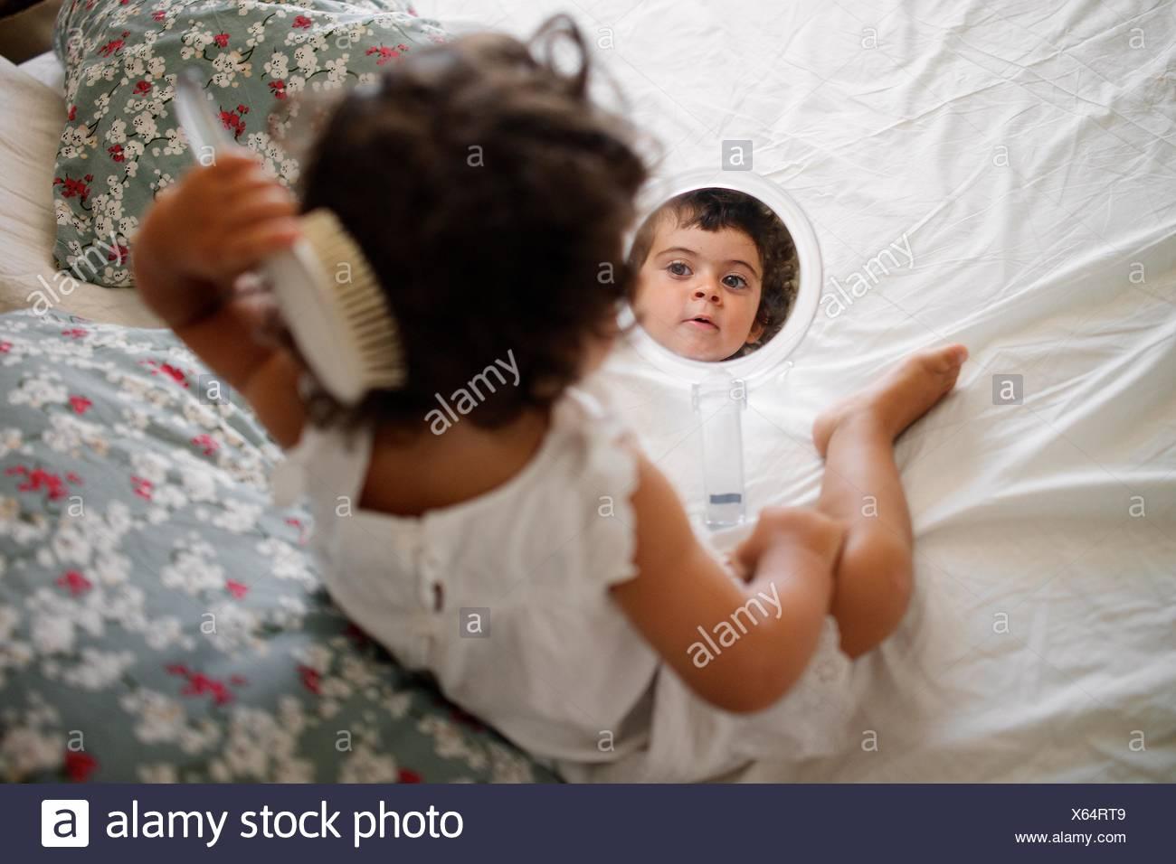 Mädchen (2-3) Kämmen Haare auf dem Bett mit Spiegel Stockfoto