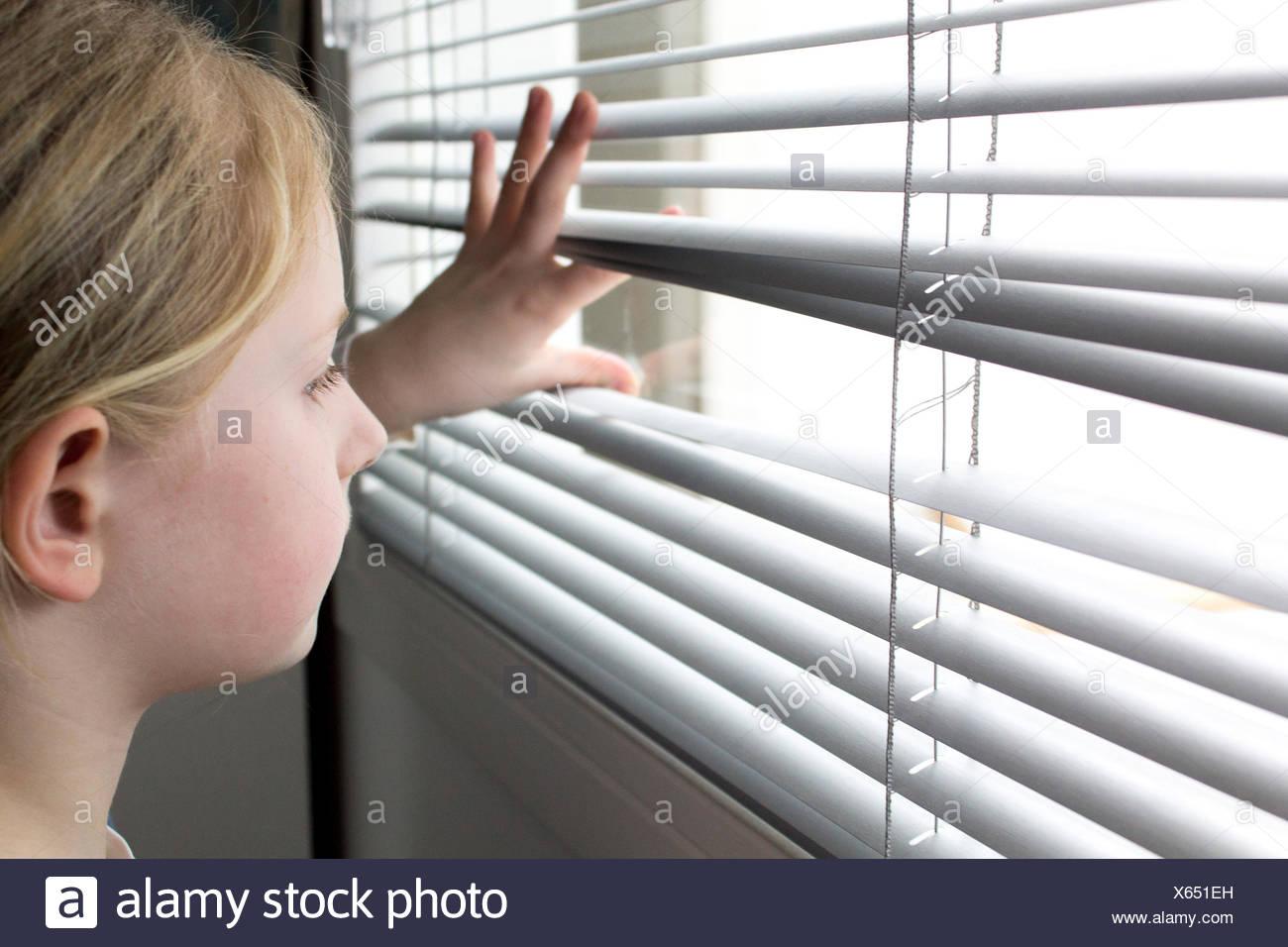 Mädchen auf der Suche durch Fenster-Vorhänge Stockbild