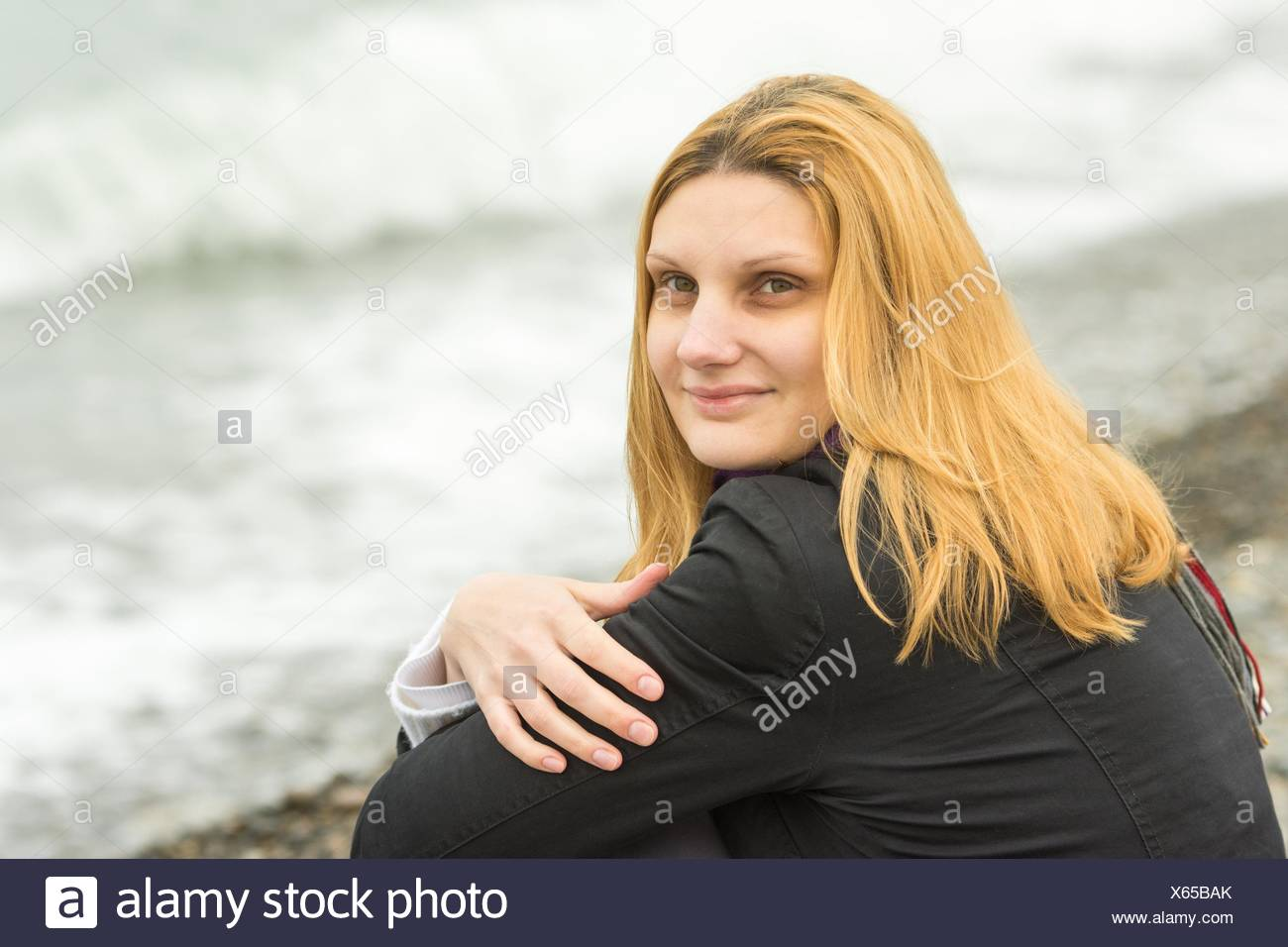 Portrait von am Strand zu sitzen geheimnisvoll lächelnden Mädchen in Wetter. Stockbild