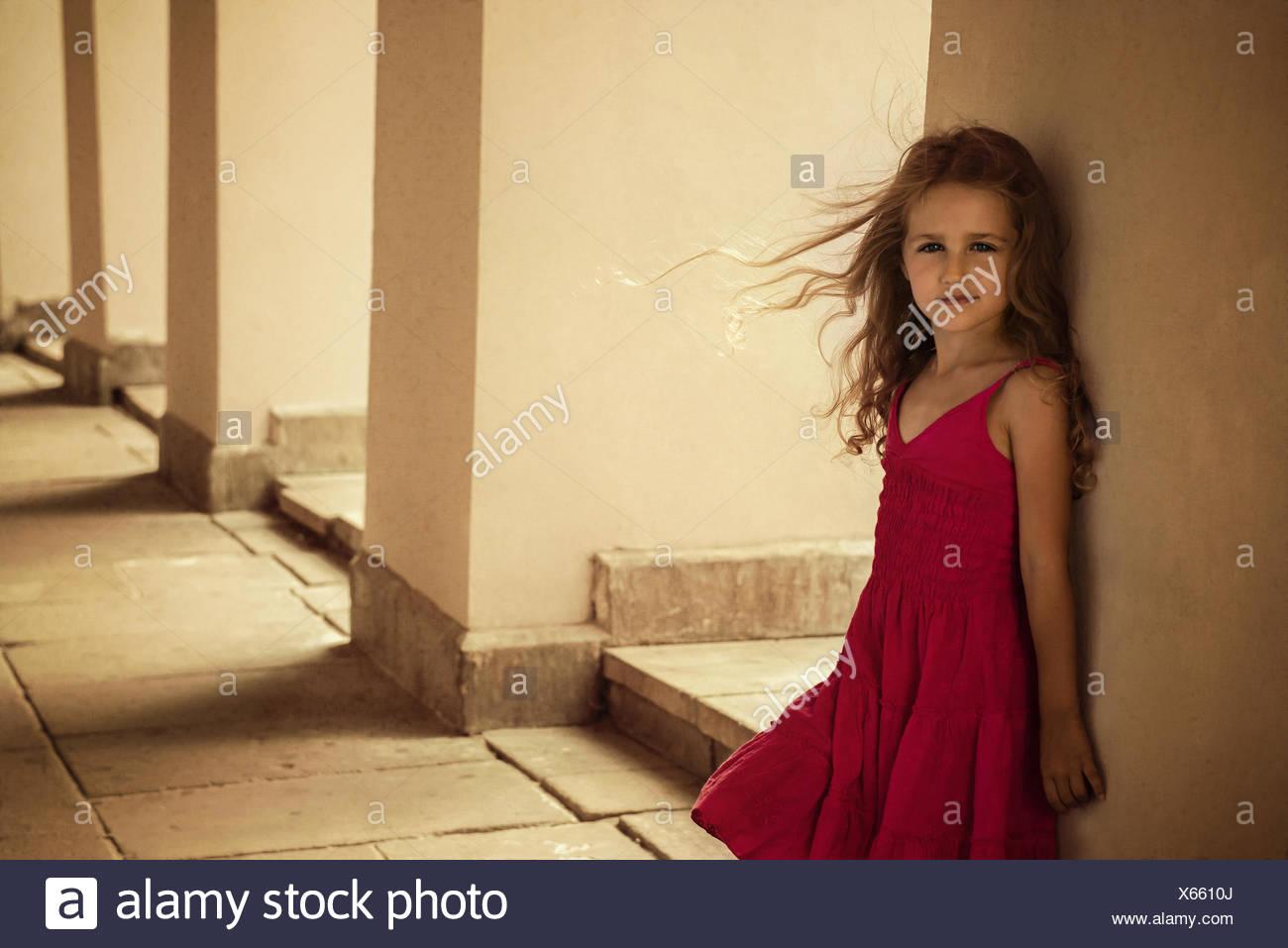Mädchen (4-5) posiert in roten Kleid Stockfoto
