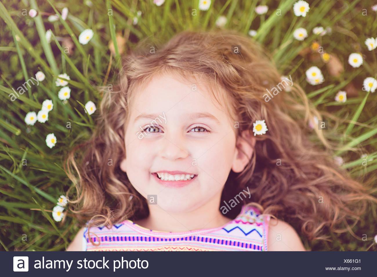 Porträt von lächelndes Mädchen im Grass liegen (4-5) Stockbild