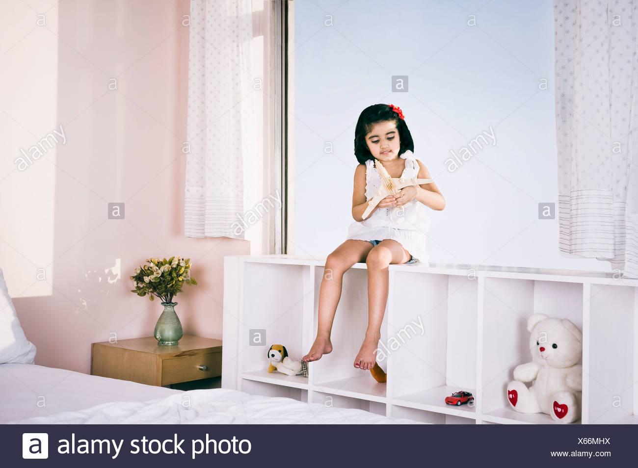 Mädchen sitzen auf einem Regal und spielen mit Spielzeugflugzeug Stockbild