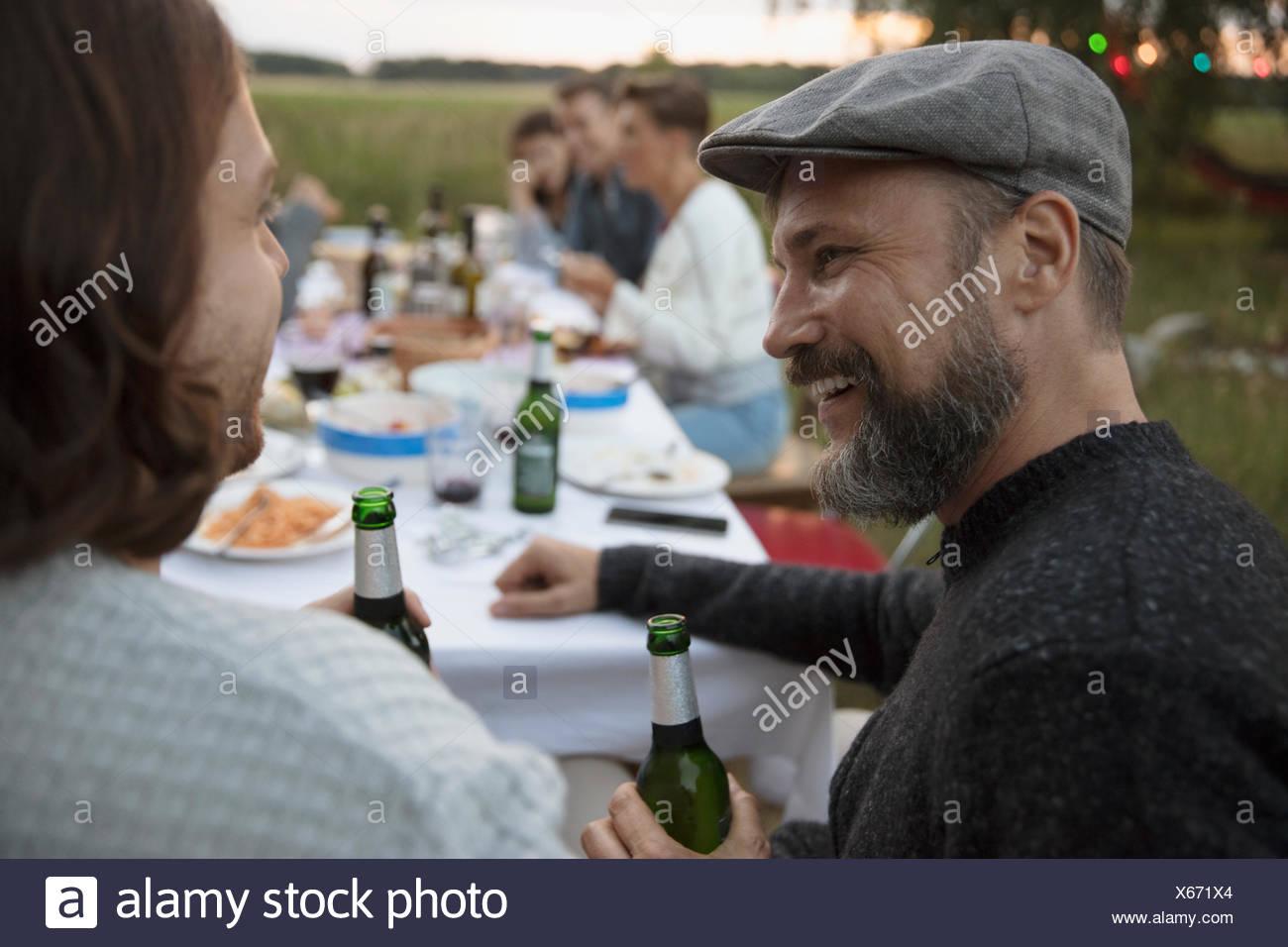 Lächelnd mann Bier trinken und reden an Freund im Summer Garden Party Abendessen Stockbild