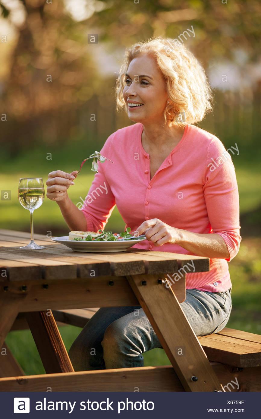 Eine reife Frau sitzen auf einer Gartenbank eine Mahlzeit Stockbild