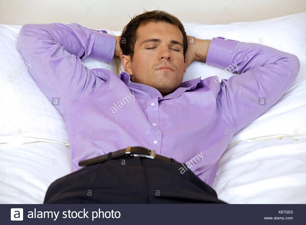 Entspannende Mann im Hotelzimmer mit Händen hinter dem Kopf, Augen geschlossen Stockbild