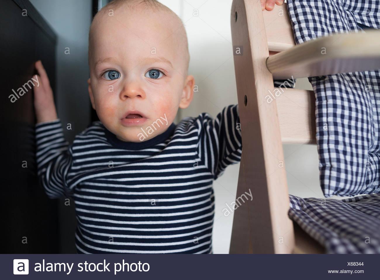 Porträt von starren Babyjungen neben Hochstuhl Stockbild