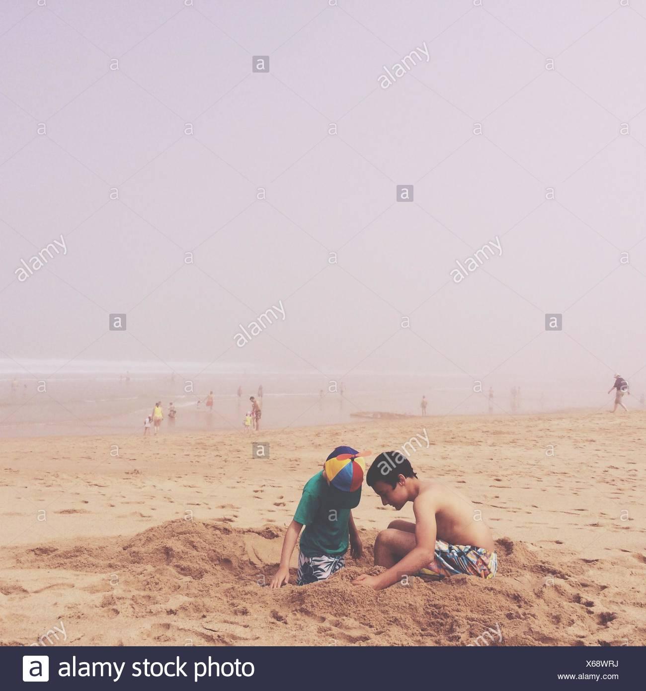 Zwei Jungs spielen mit Sand am Strand Stockbild