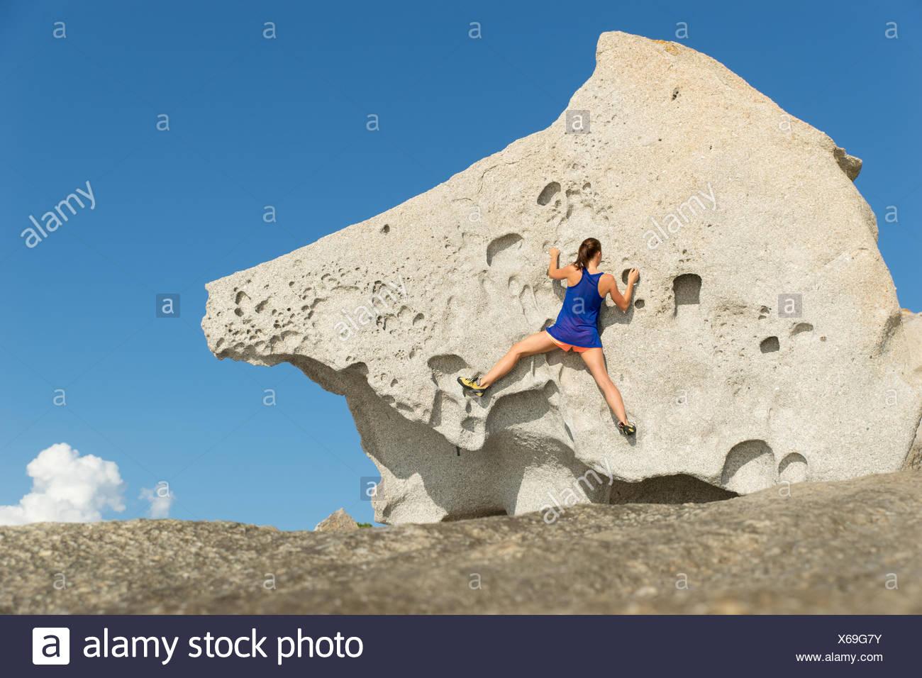 Frankreich, Korsika, junge Frau, die großen Felsen klettern Stockbild