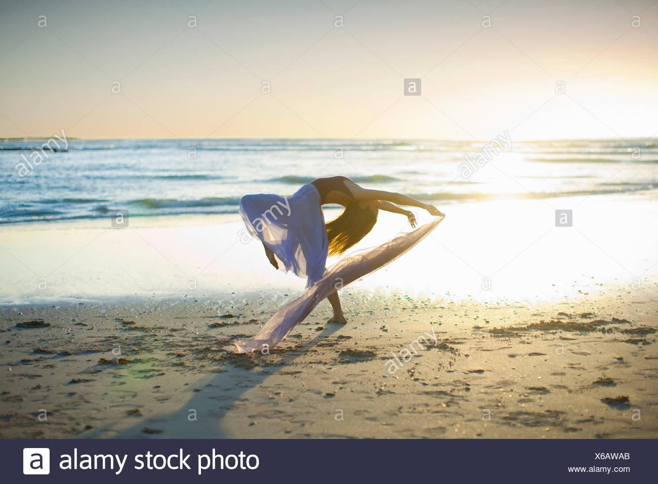 Junge Frau am sonnigen Strand tanzen Stockbild