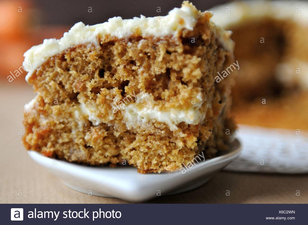 Ein einziges Stück Karottenkuchen auf einem weißen Teller Stockbild