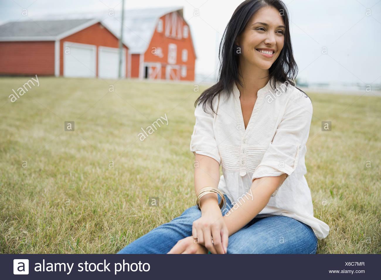 Lächelnde Frau sitzen im freien Stockfoto