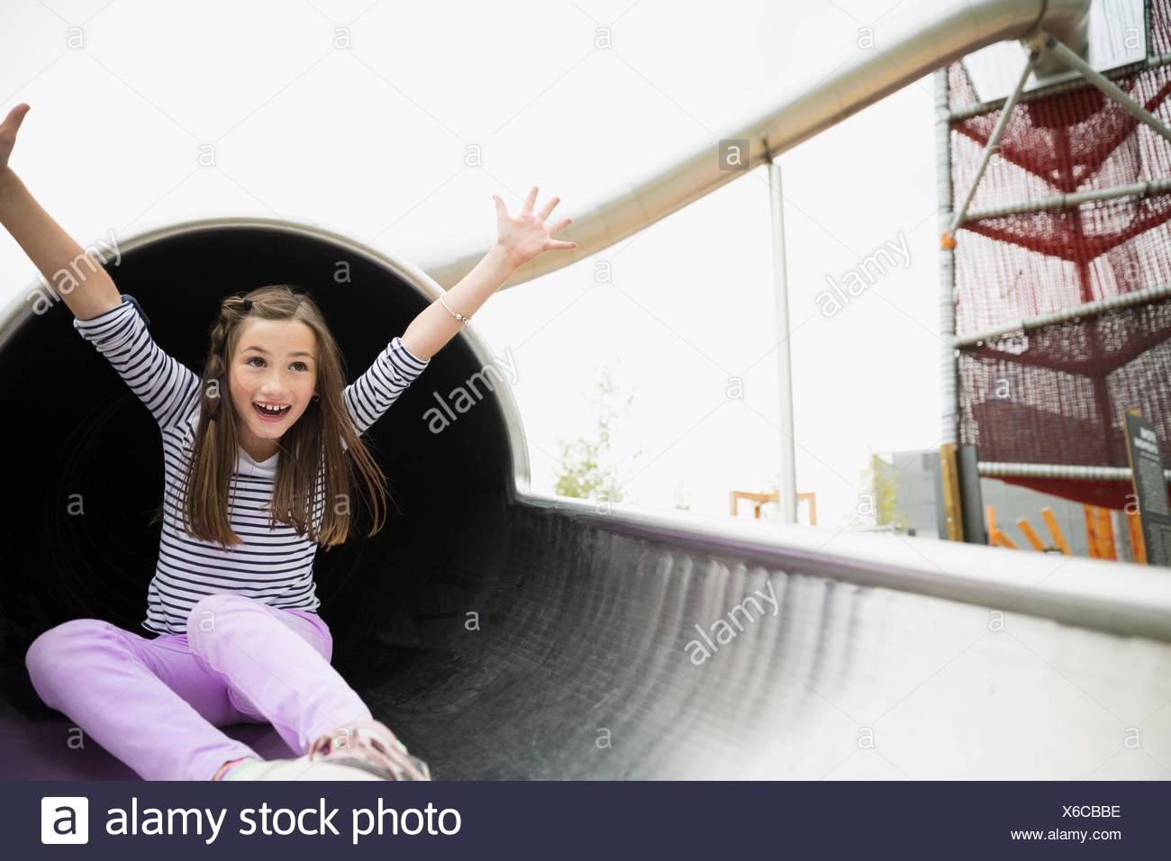 Verspielte Mädchen rutschen aus Folie Tunnel am Spielplatz Stockbild