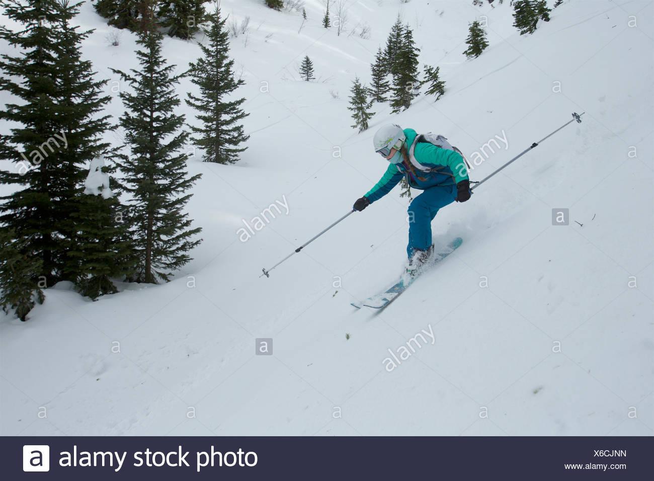 Ein jugendlich Mädchen Skitouren in den Bergen mit Nadelbäumen. Stockfoto