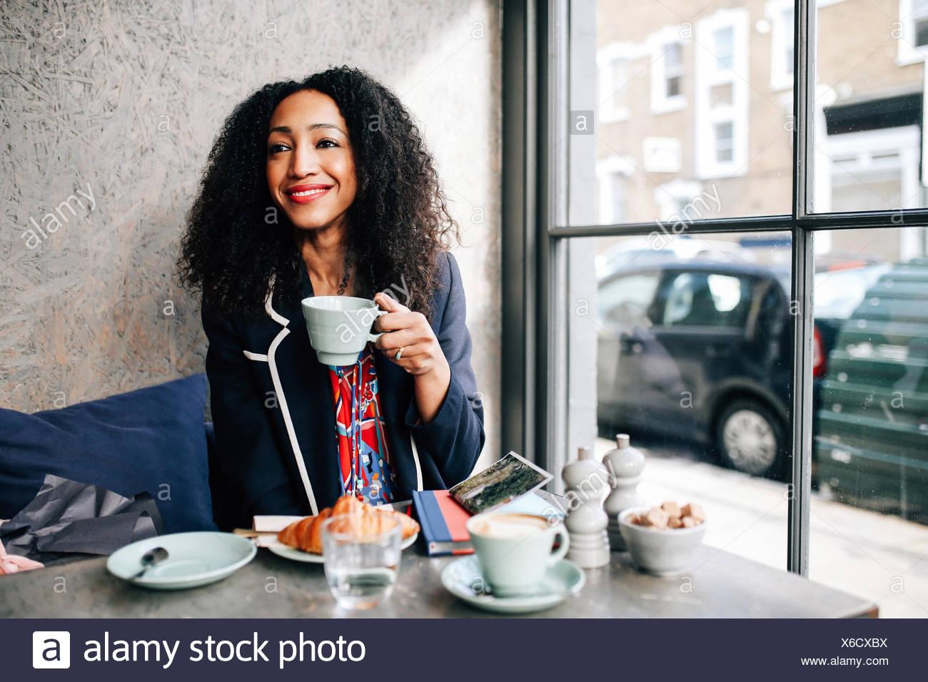 Mitte Erwachsene Frau, die Kaffeetasse im café Stockbild